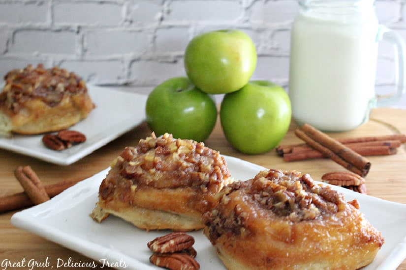 Two white plates with caramel apple pecan sticky buns on them with a glass container of milk and green apples in the background.