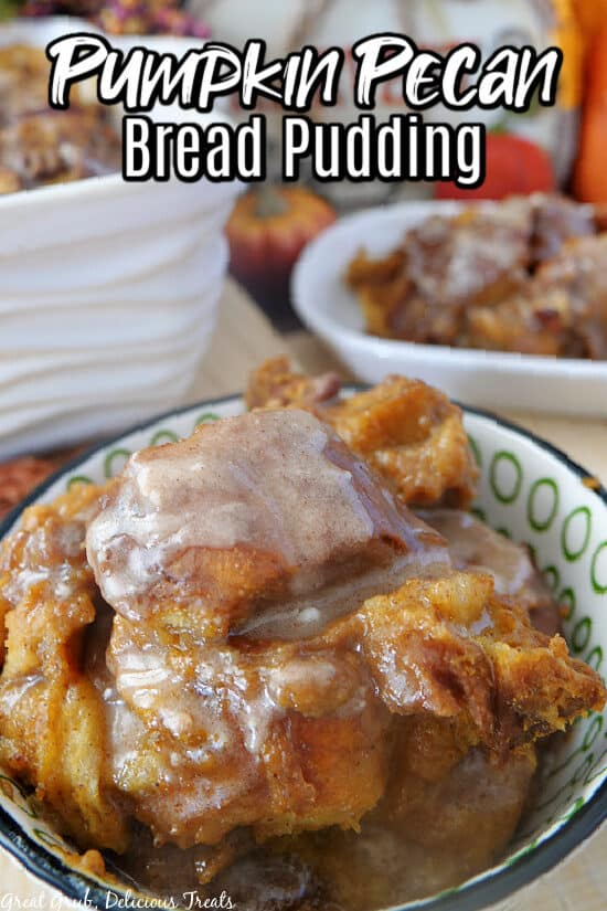 A green and white bowl filled with pumpkin pecan bread pudding with the title of the recipe at the top of the photo.