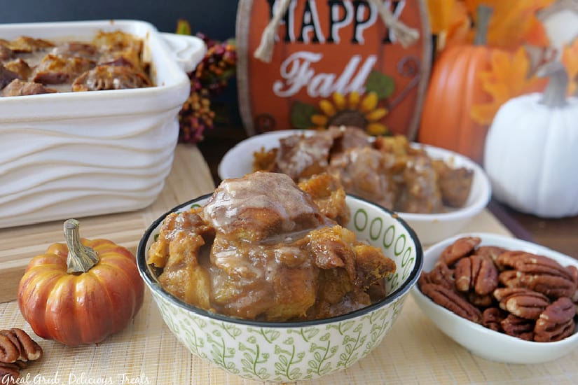 A green and white bowl filled with pumpkin pecan bread pudding with a small bowl of pecans, another bowl of bread pudding and the baking dish filled with bread pudding along with fall decorations in the background.