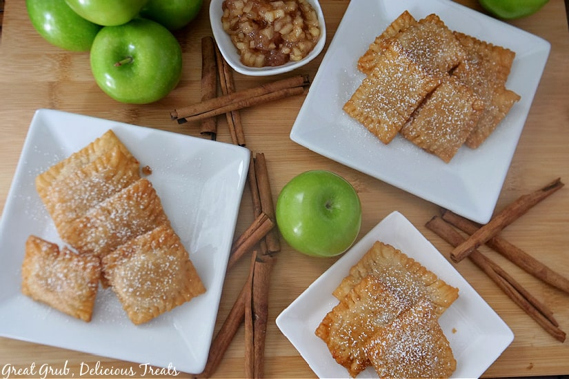 An overhead shot of 3 white plates with a stack of apple pie raviolis on each one with green apples and cinnamon sticks in the photo.