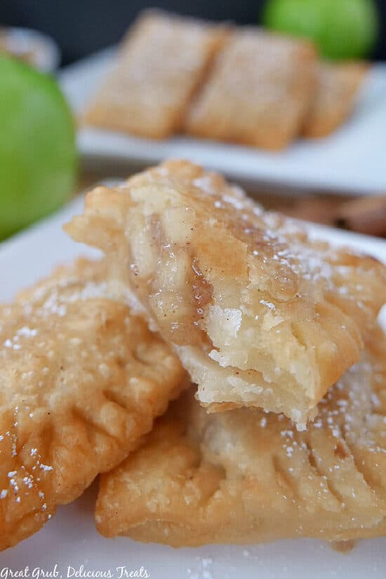 A stack of apple pie raviolis on a white plate with a bite taken out of one of them.