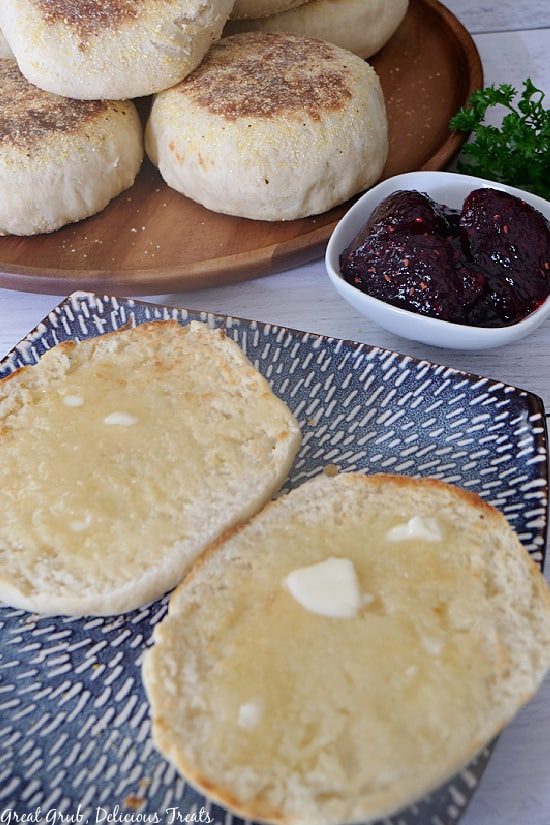 A blue plate with an English muffin cut in half with butter on them,  a small white bowl will raspberry jelly, and a brown plate in the background with English muffins on them.