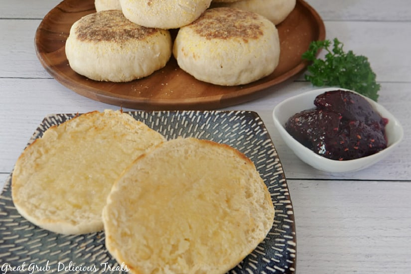 A blue plate with an English muffin cut in half, a small white bowl of jelly, and a brown plate with English muffins stacked up in the background.