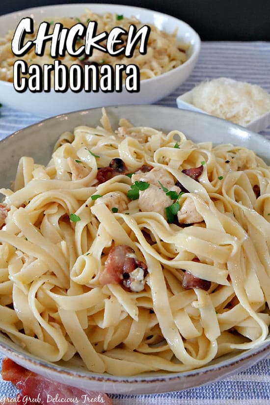 A large bowl of chicken carbonara with another large white bowl in the background filled with pasta also, and a small white bowl of grated parmesan cheese.
