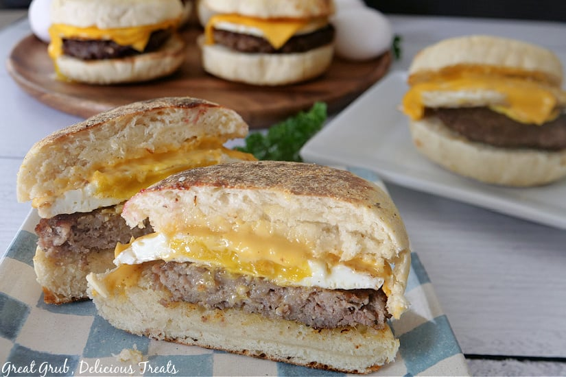 A sandwich sitting on a blue and white checkered plate and cut in half where you can see the sausage, egg, and cheese.