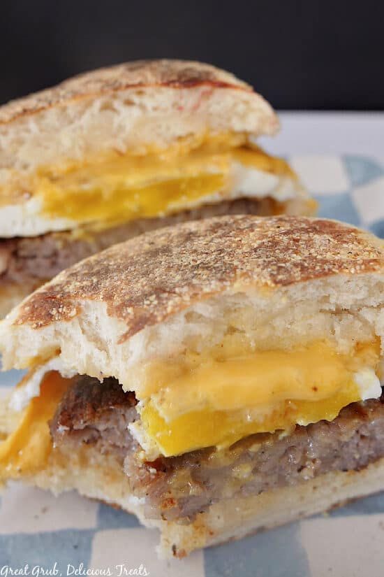 A breakfast sandwich cut in half, on a white and blue checkered plate, with a bite taken out of it.