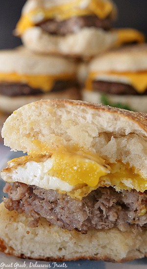 A close up photo of a breakfast sandwich with a bite taken out of it where you can see the sausage, egg, and cheese in between the English muffin.