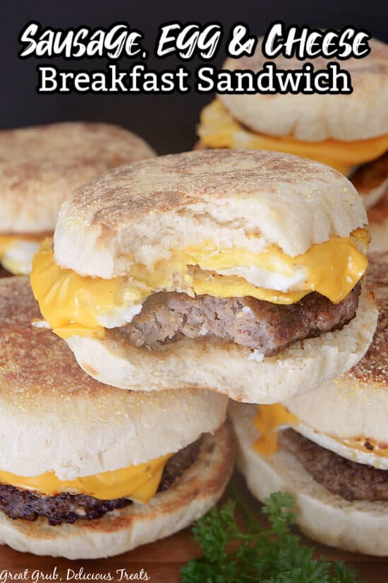 A close up of three breakfast sandwiches stacked on one another, with a bite taken out of one.