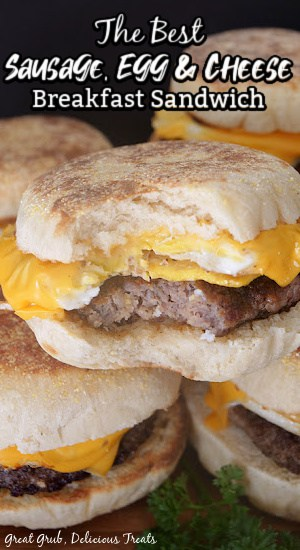 Breakfast sandwiches stacked up on each other with a bite taken out of one.