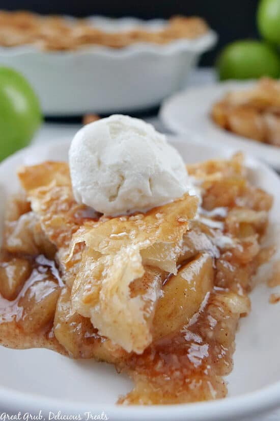 A slice of homemade apple pie o a white plate with a scoop of vanilla ice cream on top.