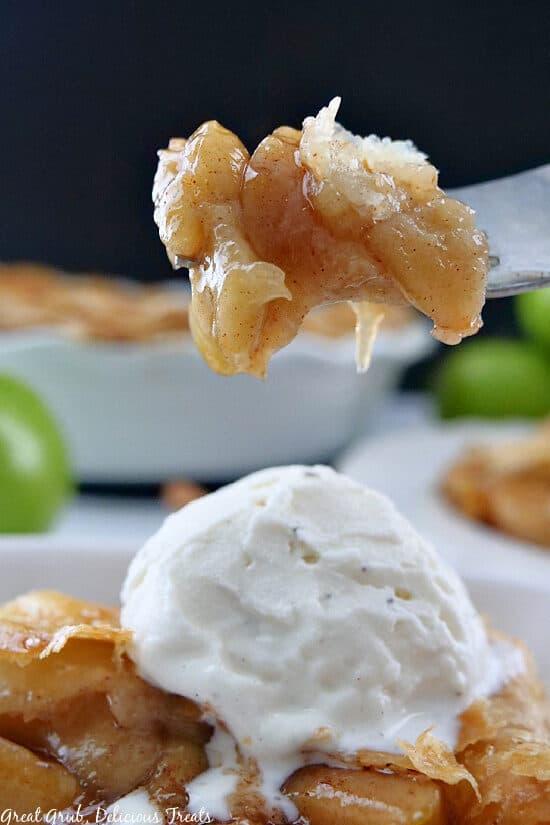 A close up photo of a bite of homemade apple pie.