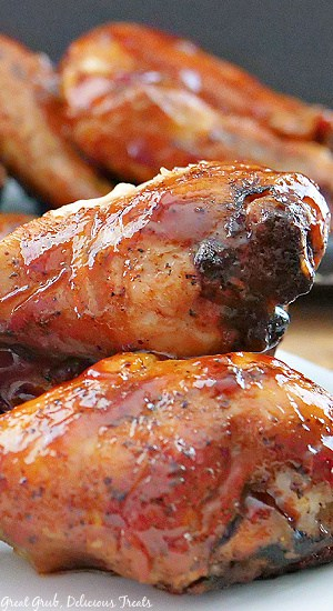 Close up picture of Honey Barbecue Drumsticks on a white plate with more drumsticks in the background.