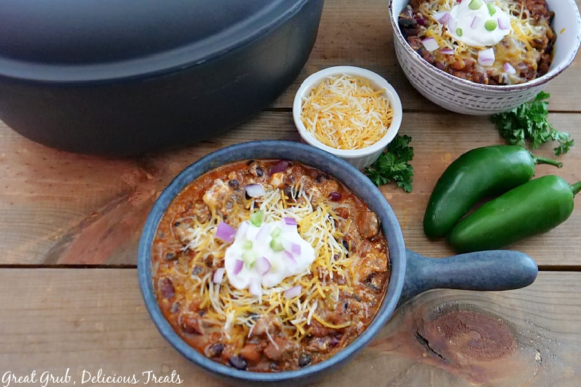 An overhead picture of chili in two bowls, topped with shredded cheese, sour cream, and red and green onions. Jalapenos, shredded cheese in a small bowl, and parsley are around the bowls of chili.