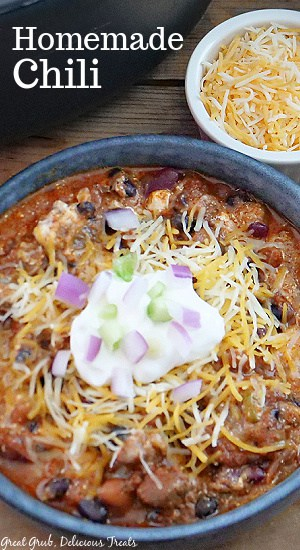 Homemade Chili in a bowl with shredded cheese, sour cream, green onions, and red onions on top.