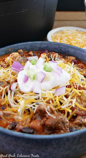 A close up picture of chili in a grey bowl with shredded cheese, sour cream, red onions, and green onions on top.