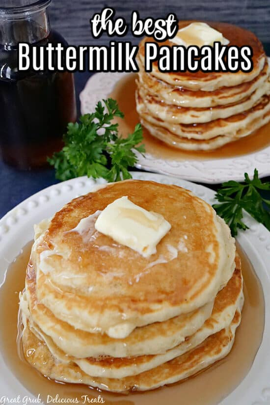 Two white plates with a stack of fluffy pancakes on each plate with butter and syrup poured over the top.
