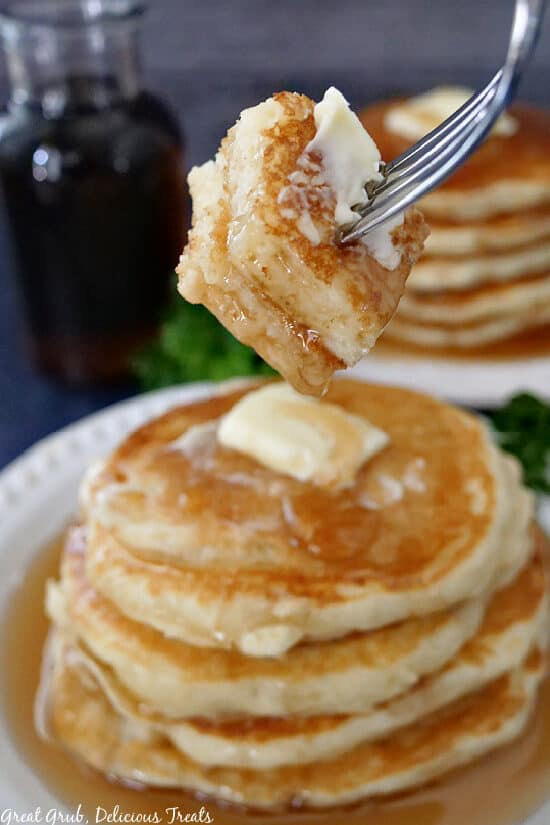 A fork with a bite of buttermilk pancakes on it held above a stack of four pancakes.