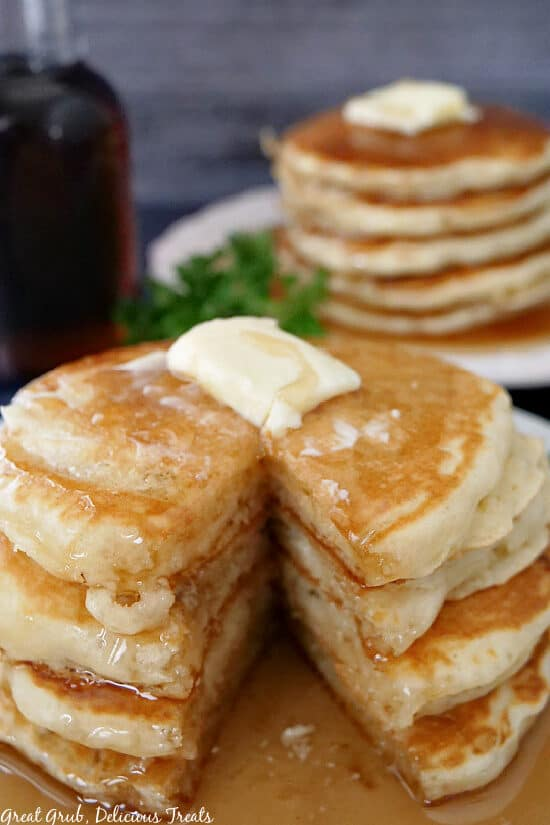 A stack of four pancakes on a white plate with a bite taken out showing the layers of pancakes.