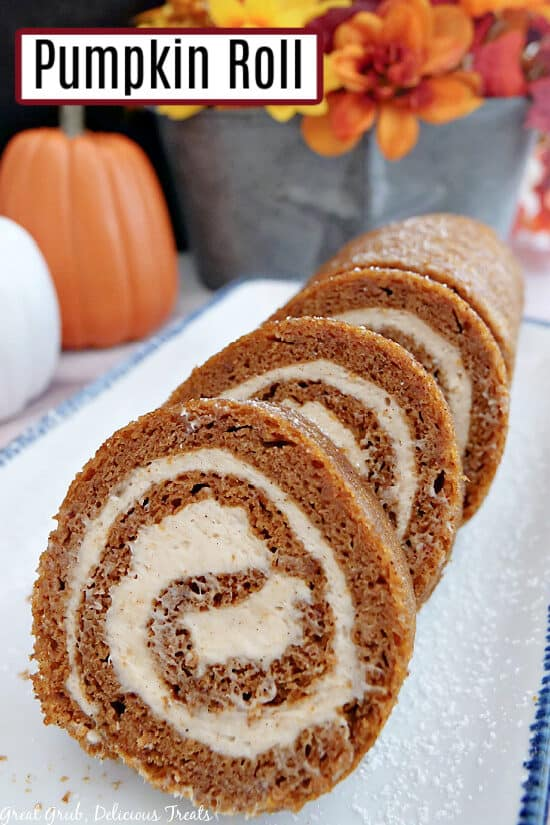 A white plate with blue trim with a pumpkin cake roll on it.