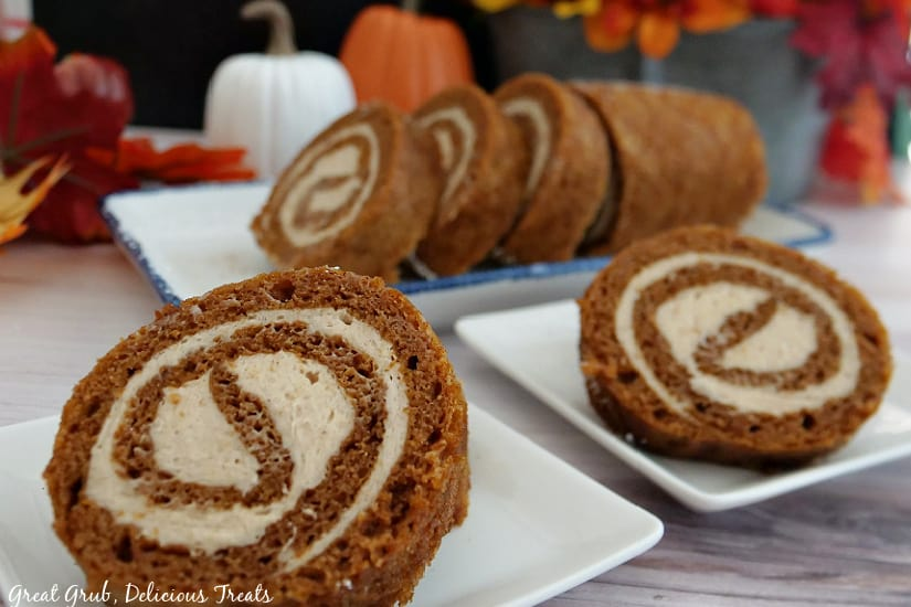 Three white plates with slices of pumpkin roll cake on them.