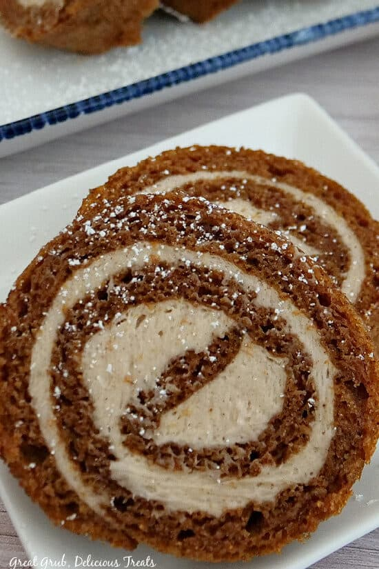 A super close up photo of two slices of pumpkin roll cake on a white plate.