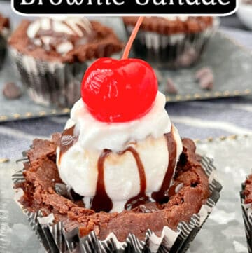 A close up photo of one brownie cup, in a black and white plaid cupcake liner, topped with ice cream, hot fudge, and a cherry.