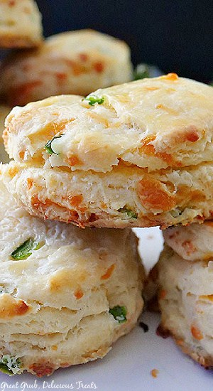A close up photo of three buttermilk biscuits with cheese and diced jalapeños on a white plate.