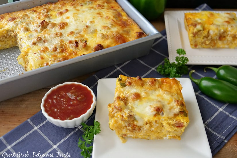 A serving of breakfast casserole on a white plate with a baking dish dilled and another white plate with the casserole on it.