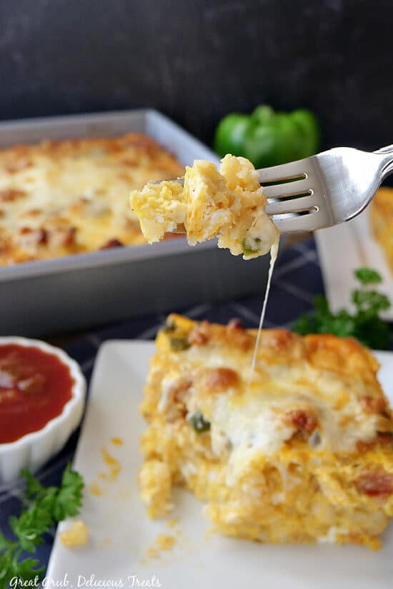 A close up of a fork with a bite of breakfast casserole on it.