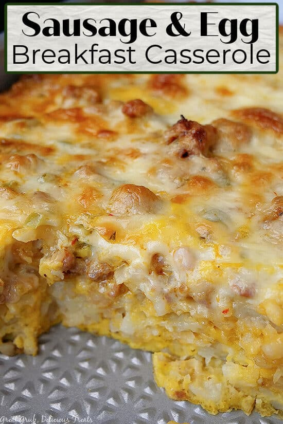 A close up photo of sausage and egg breakfast casserole in a baking dish with a serving taken out.