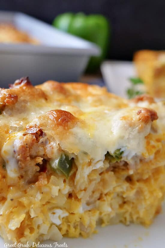 A close up photo of a serving of sausage and egg breakfast casserole on a white plate.