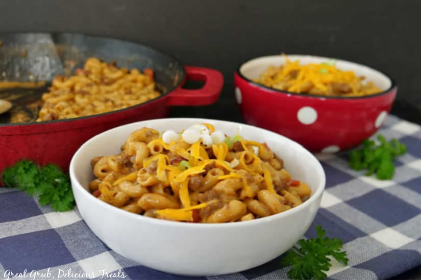 A white bowl and a red bowl filled with chili mac and a red cast iron pan in the background.
