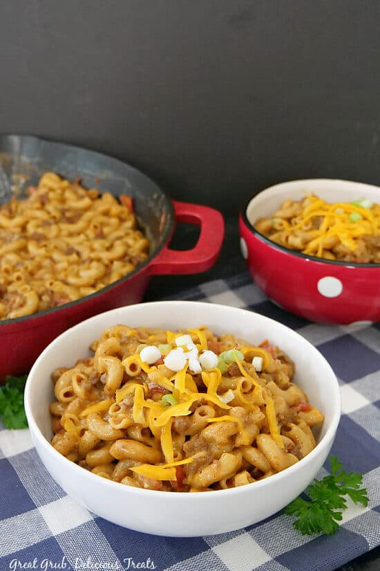 A white bowl, a red bowl and a red cast iron pan with homemade chili mac in them, and place on a white and blue checkered towel.